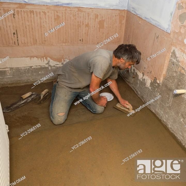 Stock Photo: A builder floating up the top coat of a concrete floor in a bathroom.