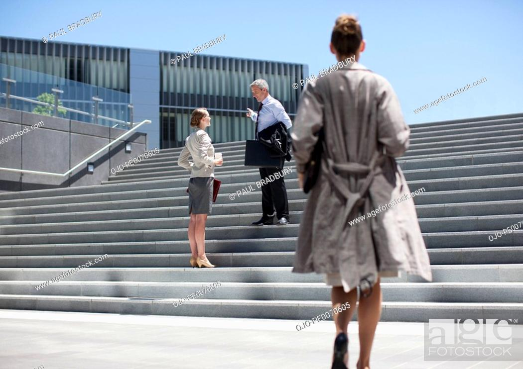 Stock Photo: Business people talking on steps outdoors.