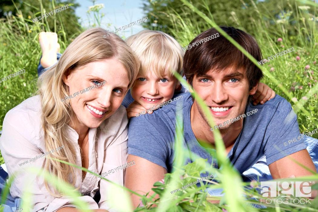 Stock Photo: Germany, Cologne, Family lying in meadow, smiling, portrait.