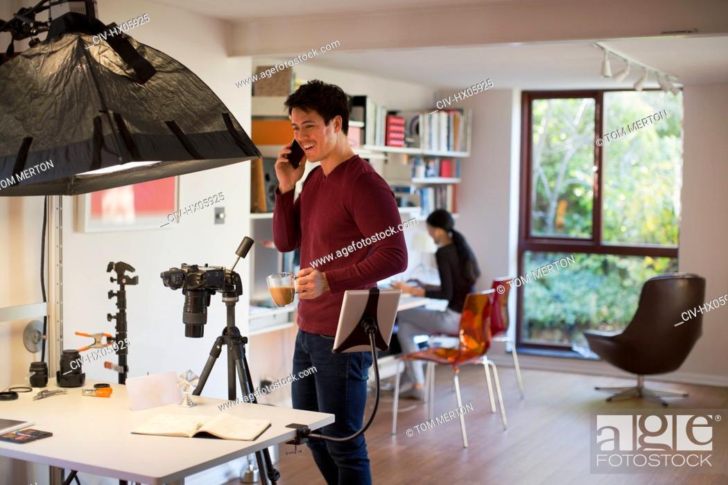 Stock Photo: Male photographer working in studio, taking coffee break.
