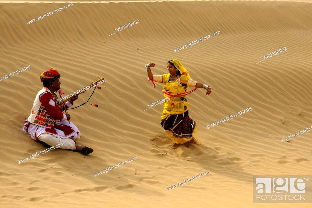 Stock Photo: Couple playing folk music and dancing in sand dunes , Jaisalmer , Rajasthan , India MR769A.