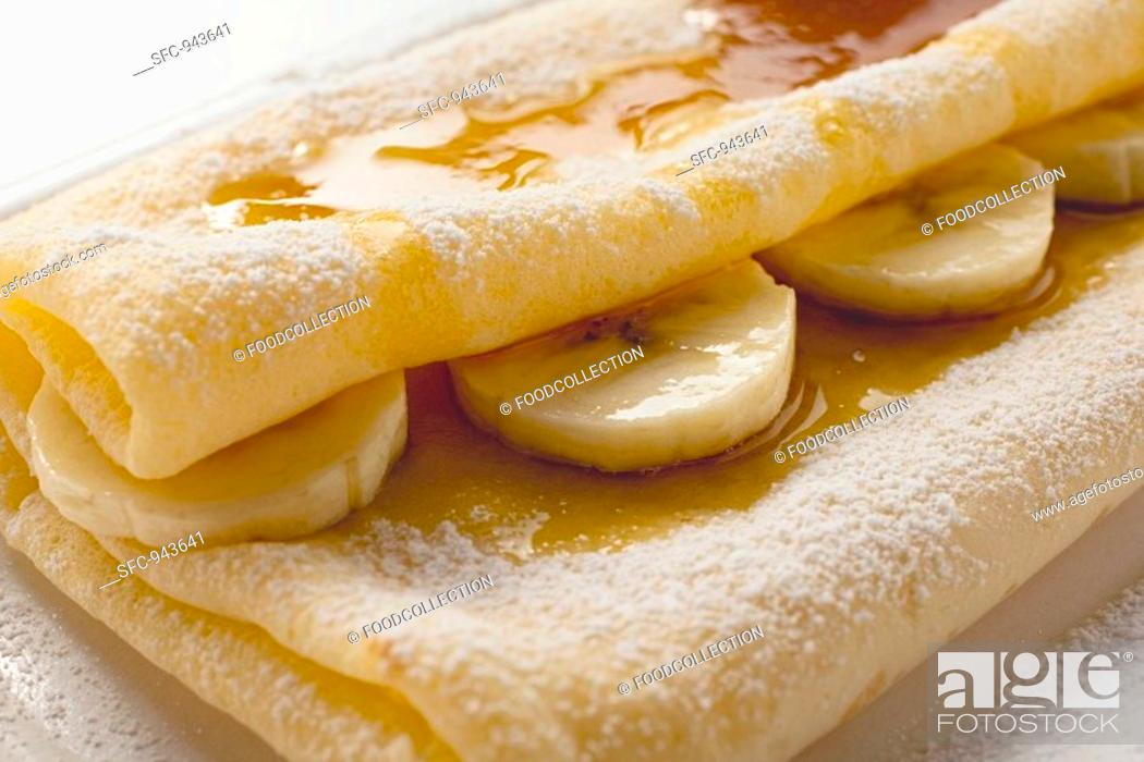 Stock Photo: Crêpes with bananas and maple syrup.