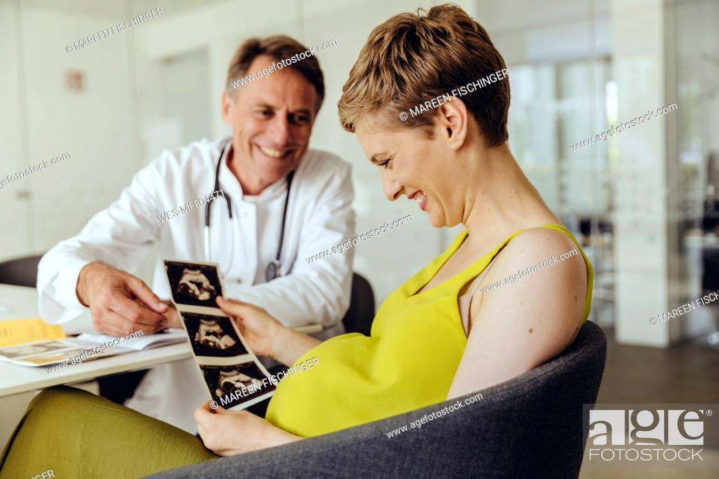 Stock Photo: Pregnant woman discussing ultrasonic scans with her doctor.