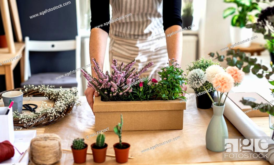 Stock Photo: Close-up of woman with flowers inside a cardboard box on table.