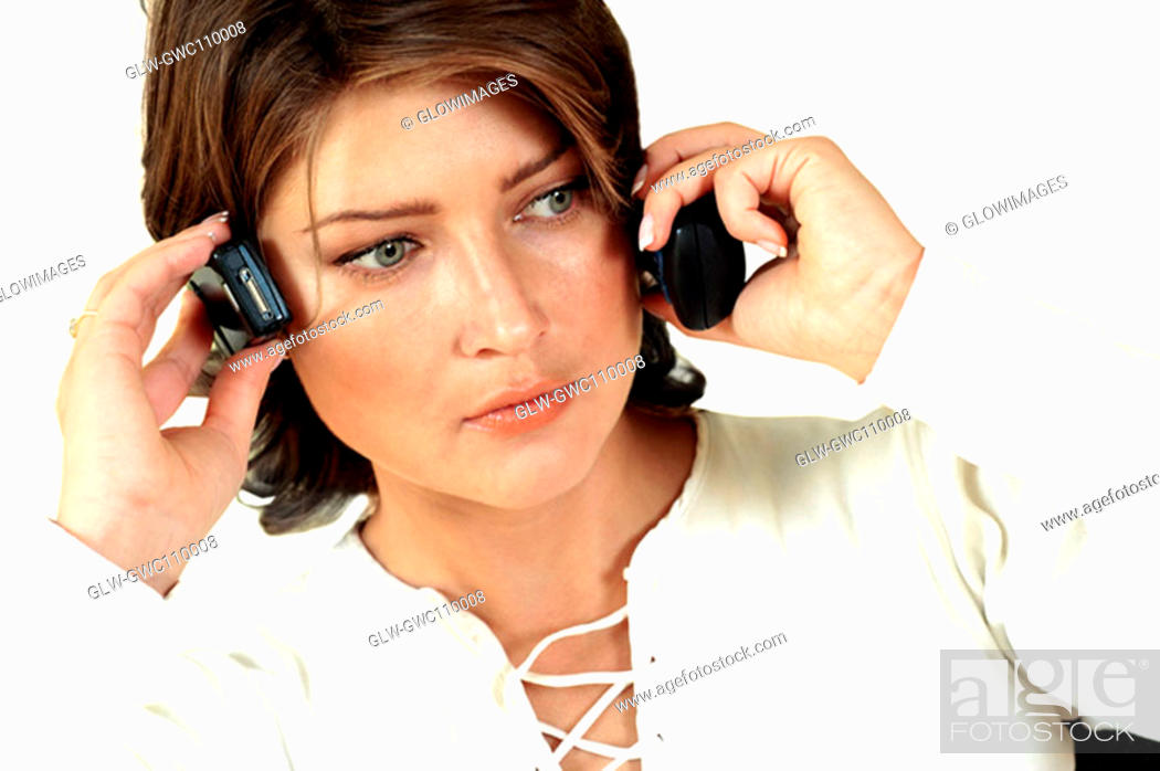 Stock Photo: Close-up of a businesswoman using two mobile phones.