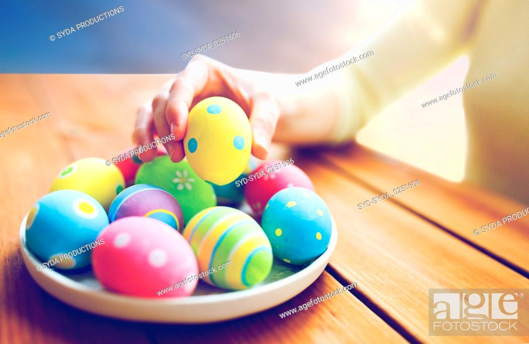 Stock Photo: close up of woman hands with colored easter eggs.