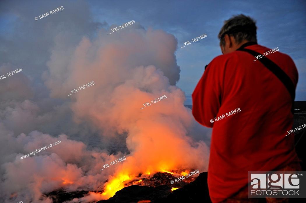 Stock Photo: Woman watching steam rising off lava flowing into ocean, Kilauea Volcano, Big Island, Hawaii Islands, USA.