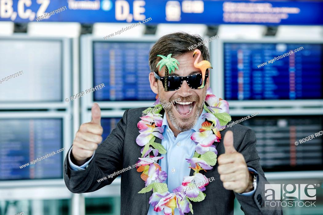 Stock Photo: Happy businessman dressed up as tourist at the airport.