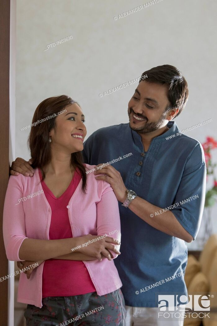 Stock Photo: Man with arms on woman's shoulders smiling at her.
