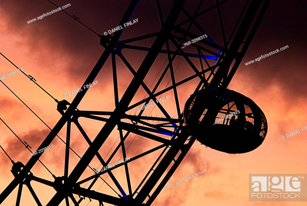 Stock Photo: A pod of the London Eye seen against a very dramatic sunset, and with a very dark cloud directly overhead, in the heart of London, England, on a Winters evening.