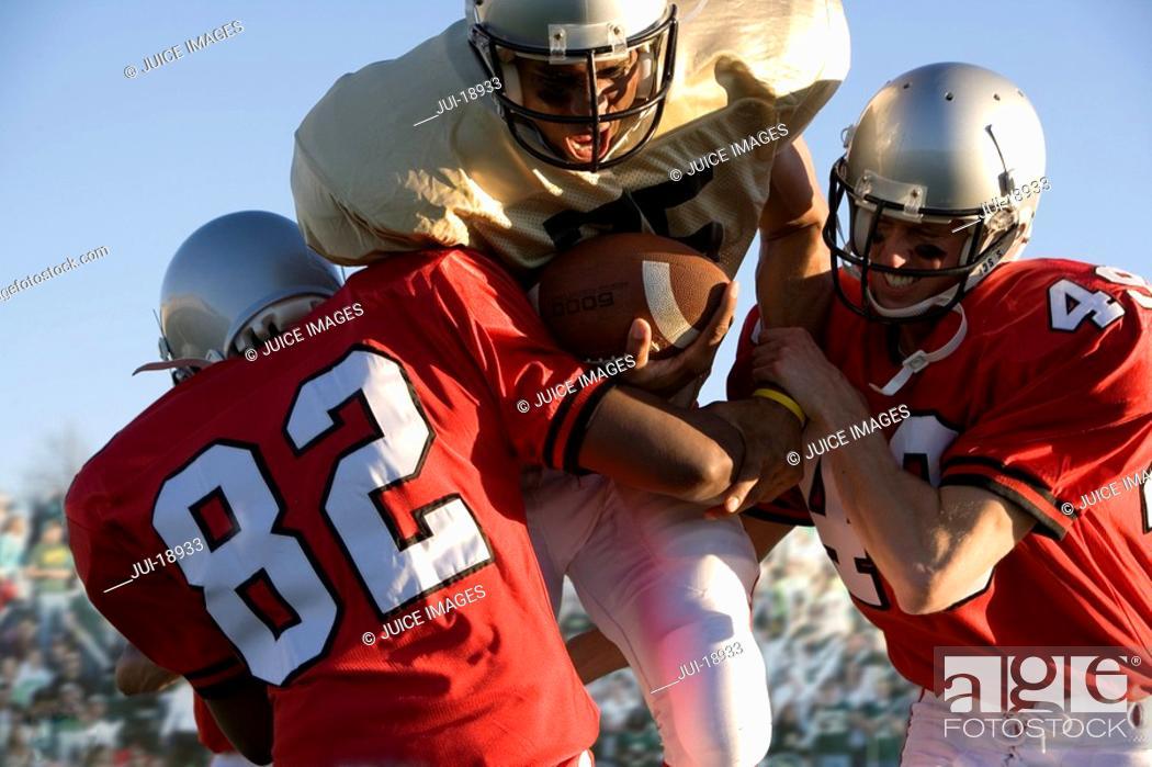 Stock Photo: Defenders tackling running back carrying football.