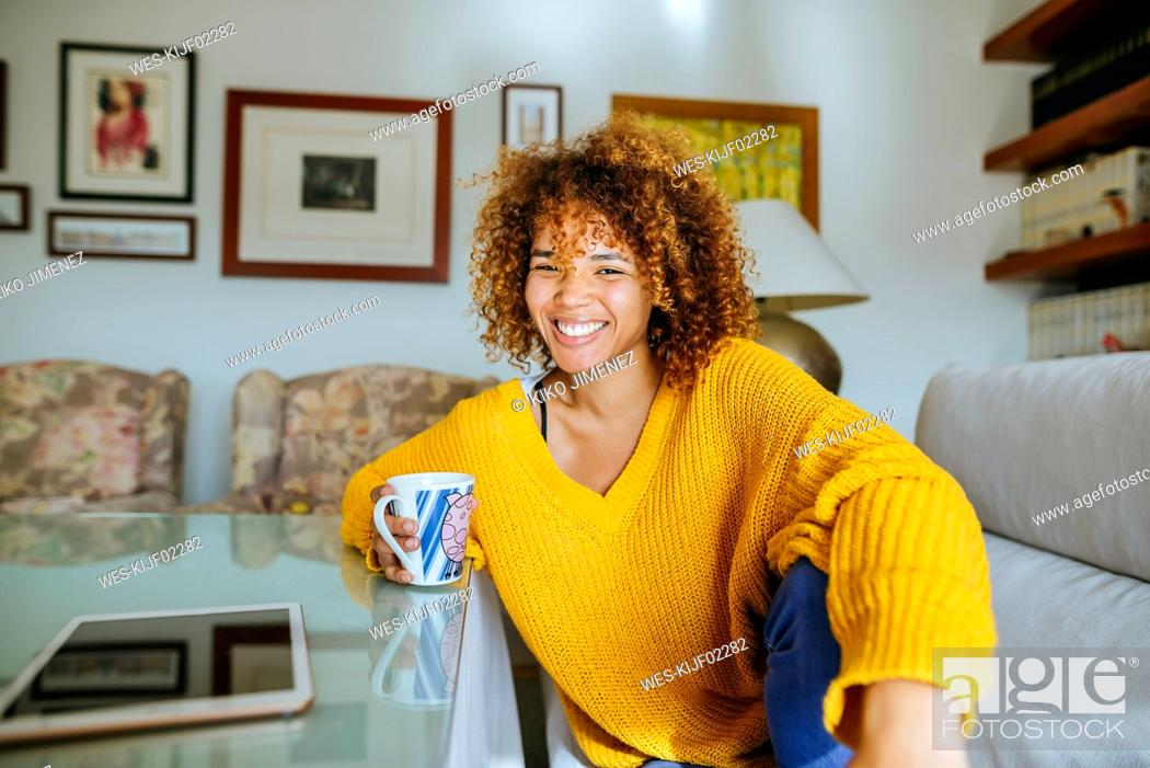 Stock Photo: Portrait of happy young woman with curly hair holding mug at home.