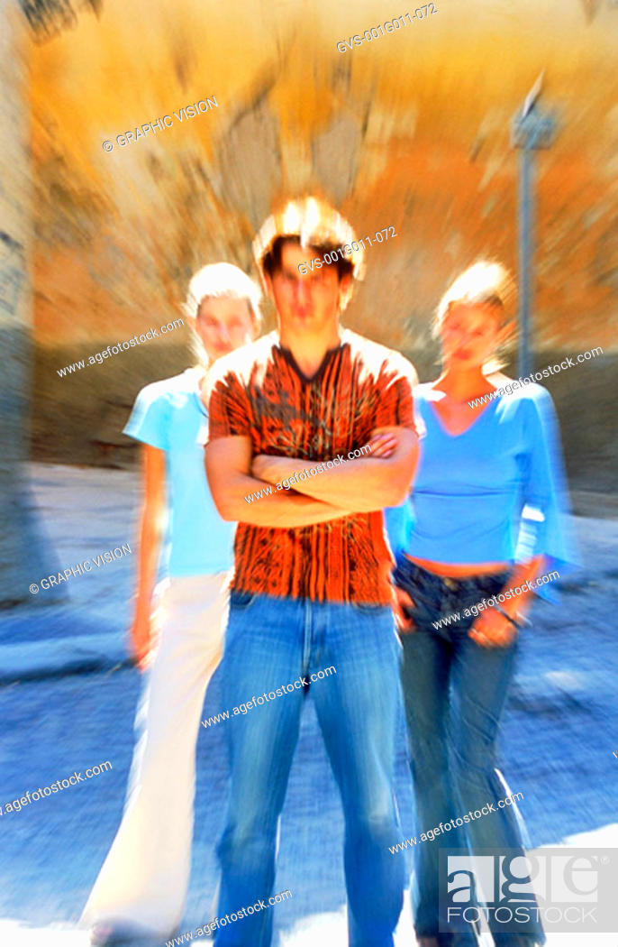 Stock Photo: Blurred portrait of a young man standing with two young women.