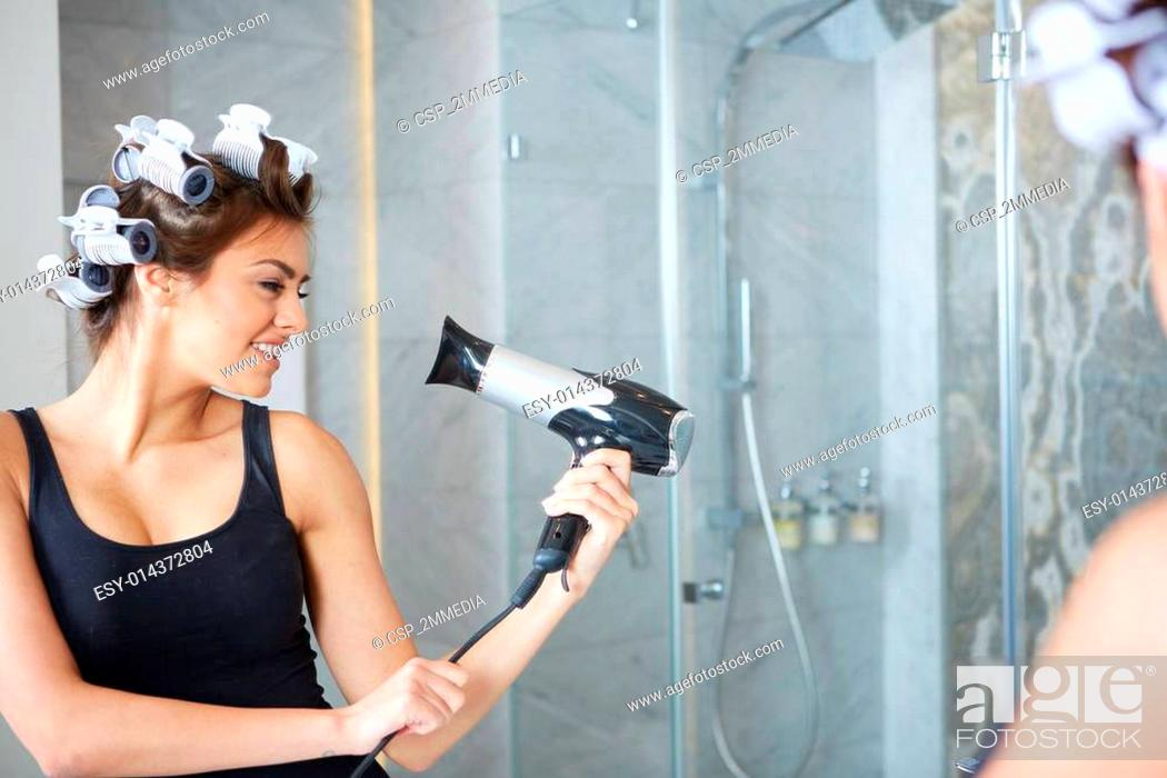 Photo de stock: young woman putting curlers in her hair, bathroom.