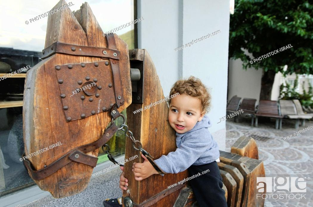 Stock Photo: young child of two plays on a wooden horse Photographed in Austria.