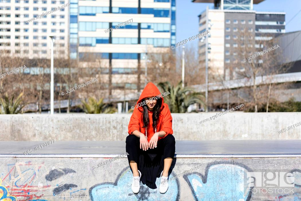Stock Photo: Young contemporary dancer wearing red hoodie shirt, sitting on the floor with city in the background.