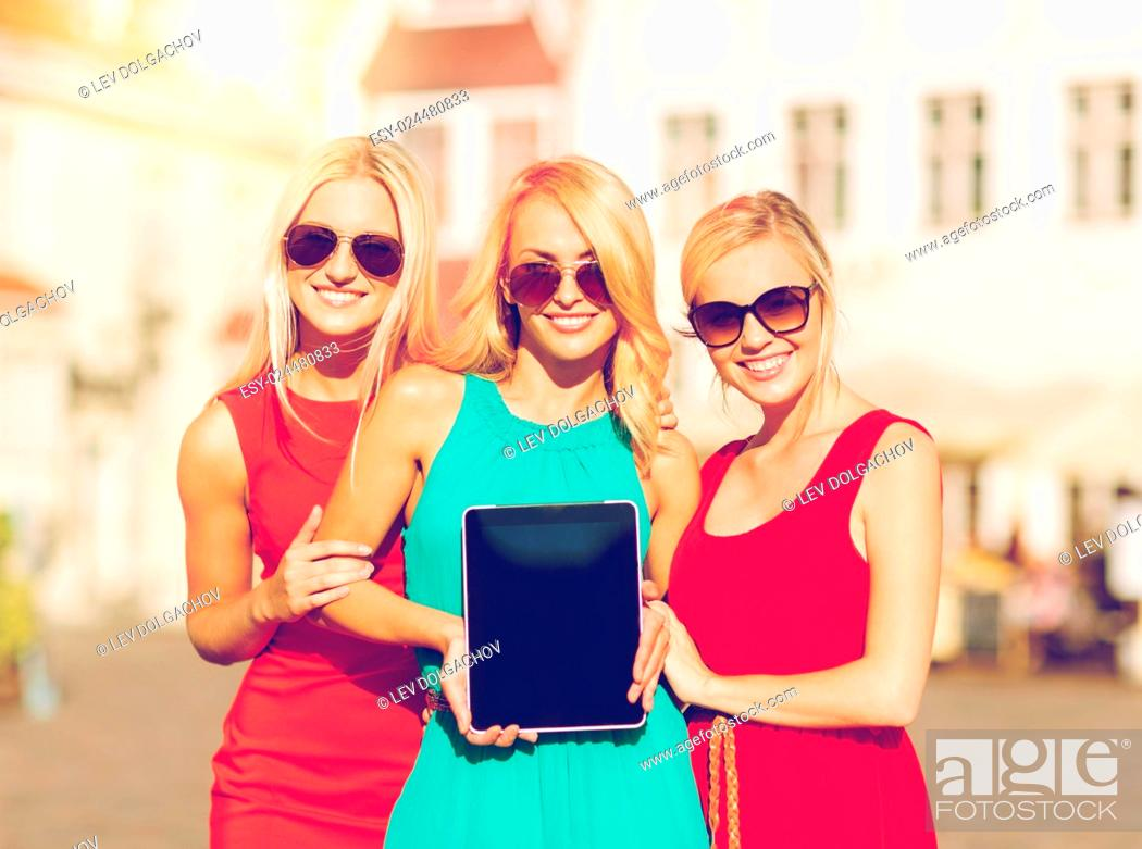 Stock Photo: holidays and tourism concept - beautiful blonde girls toursits showing tablet pc with blank screen in the city.