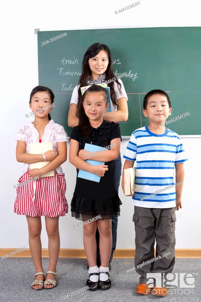 Stock Photo: Child, Children standing and holding books with teacher in the classroom.