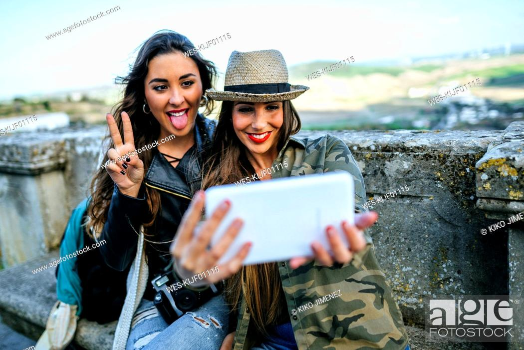 Stock Photo: Two happy young women on a trip taking a selfie with a tablet.