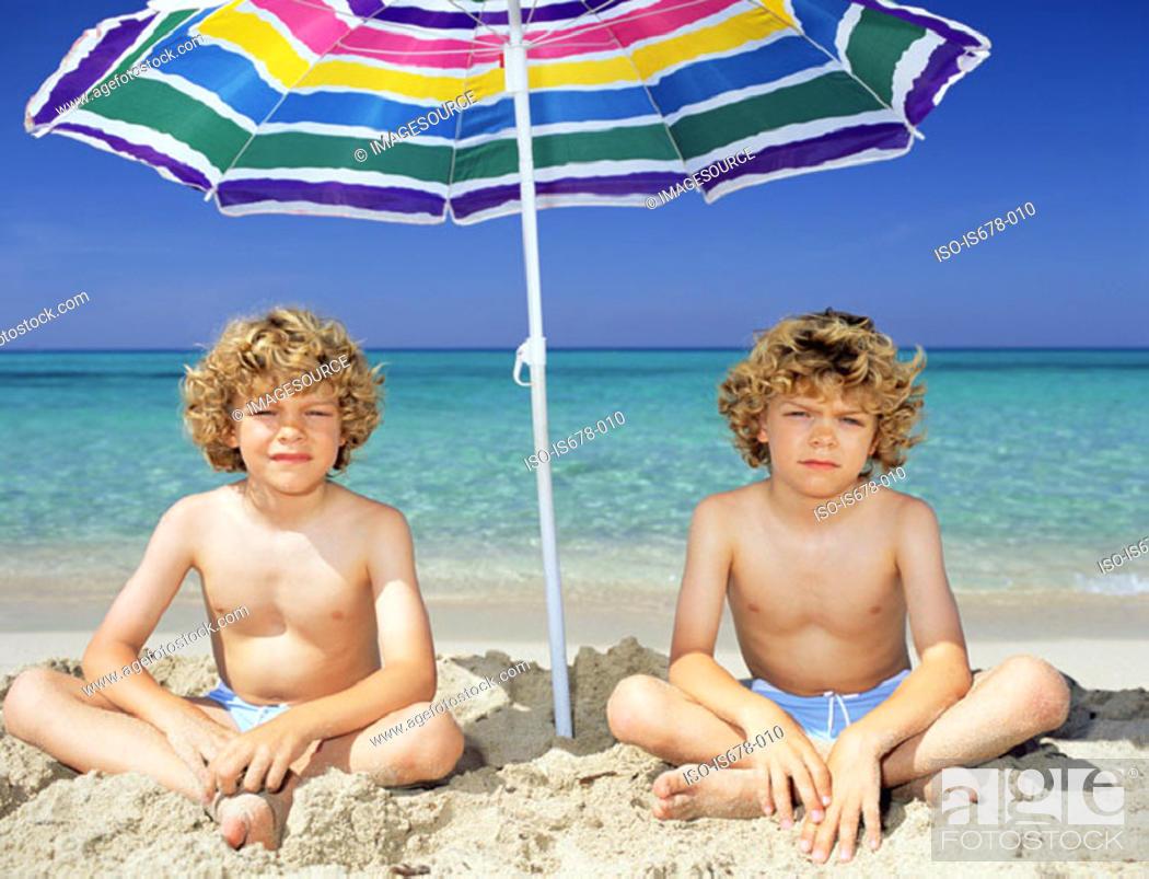 Stock Photo: Twin boys under a sun umbrella.