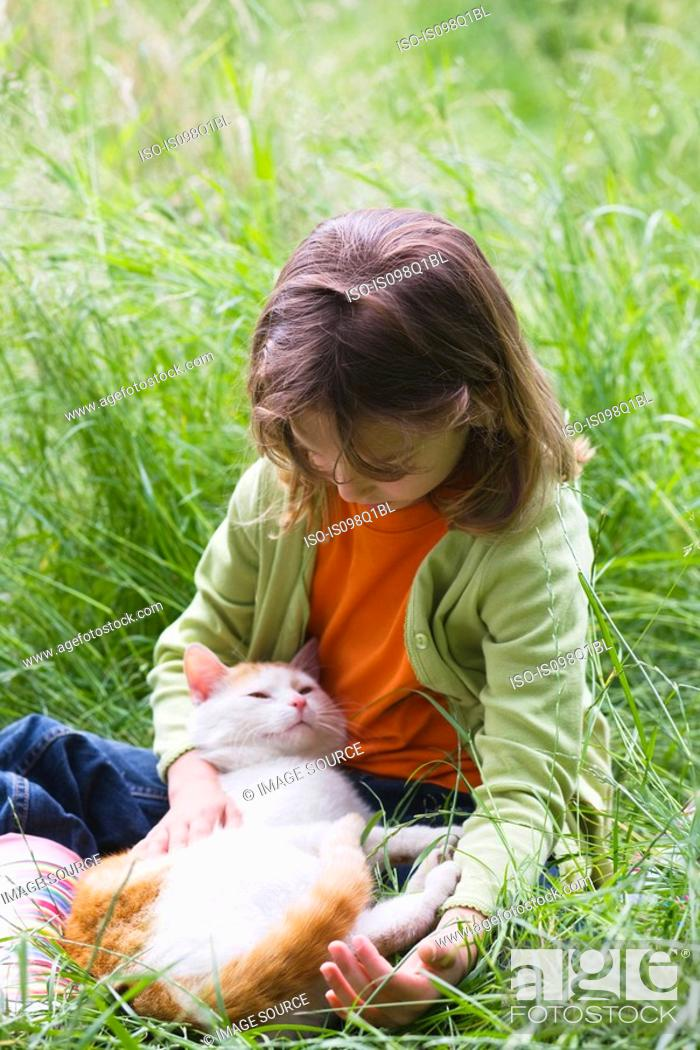 Stock Photo: A girl stroking a cat.