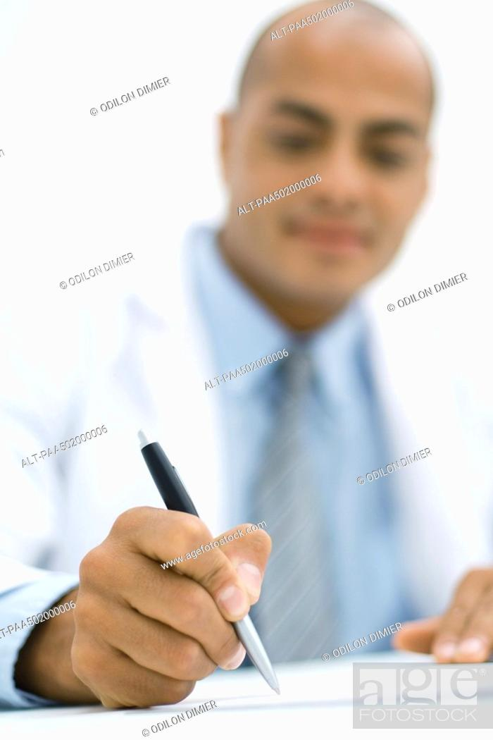 Stock Photo: Doctor writing a prescription, focus on hand in the foreground.