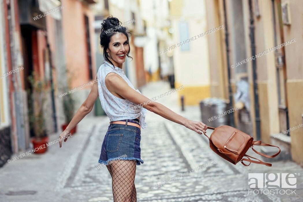 Stock Photo: Fashionable woman with small backpack in the city.