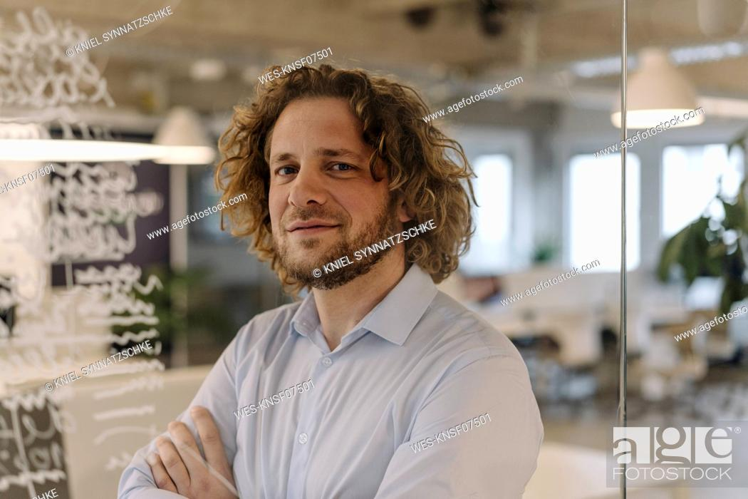 Stock Photo: Portrait of confident businessman behind a glass pane in office.