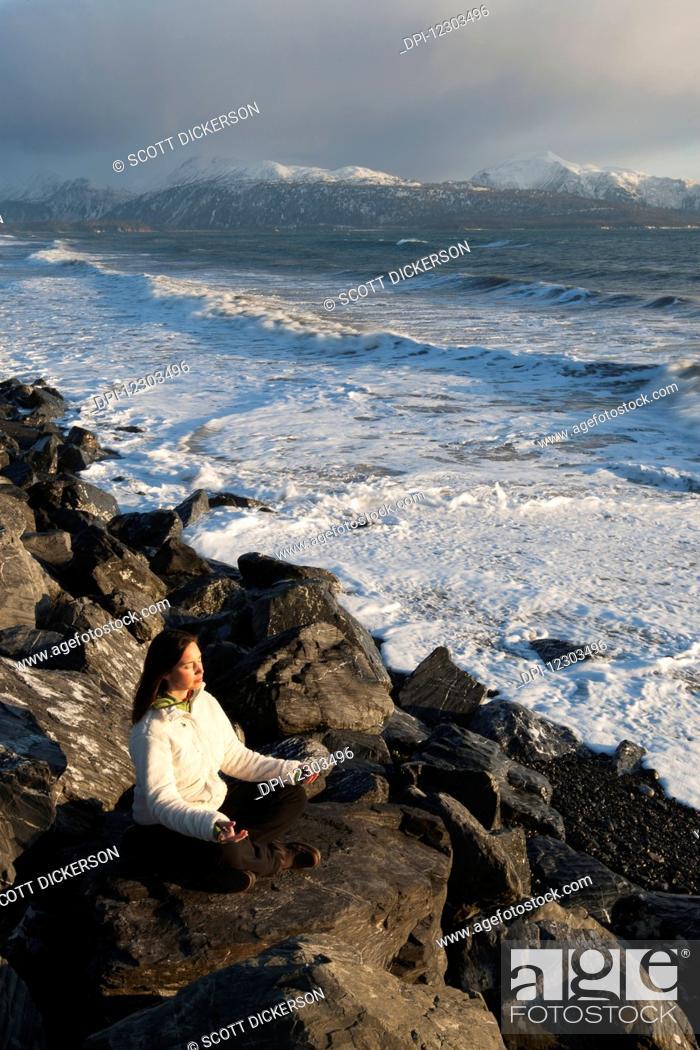 Stock Photo: Woman practicing meditation on a rocky beach, Homer Spit, Southcentral Alaska.