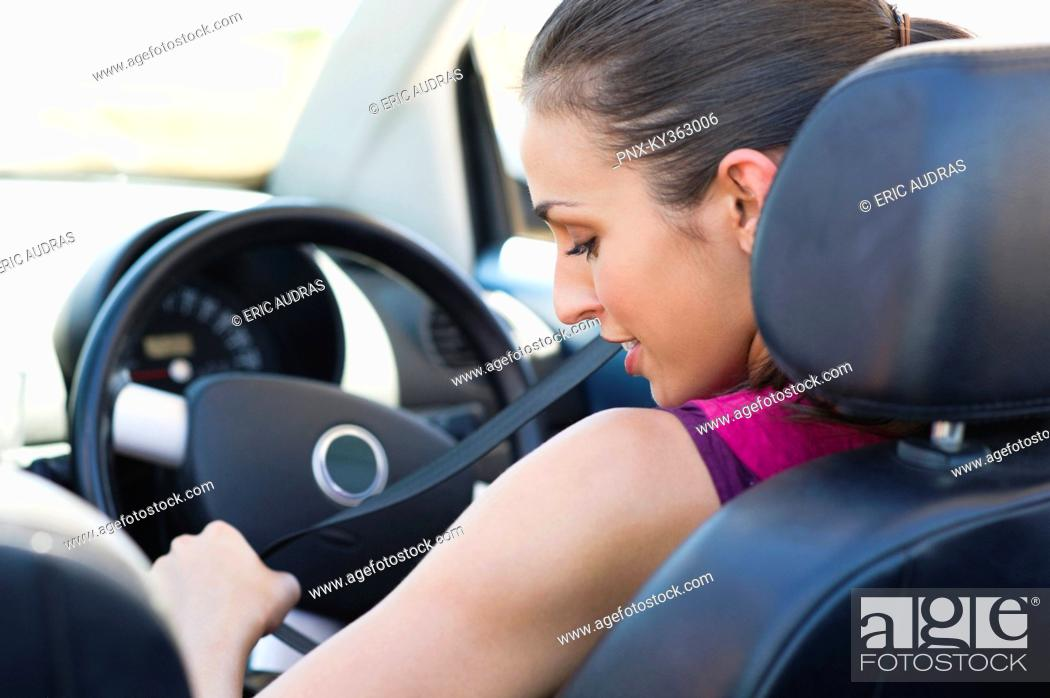 Stock Photo: Young woman wearing a seat belt.