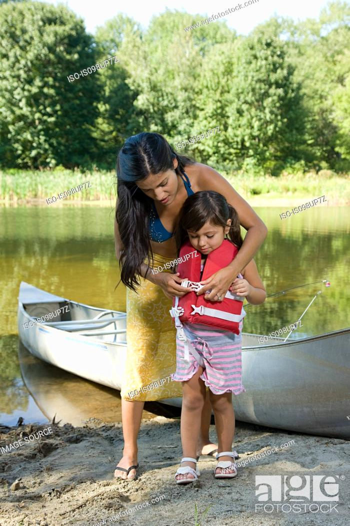 Stock Photo: Mother putting lifejacket on daughter.