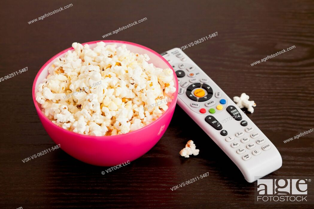 Imagen: USA, Illinois, Metamora, Bowl of popcorn and remote control on table.