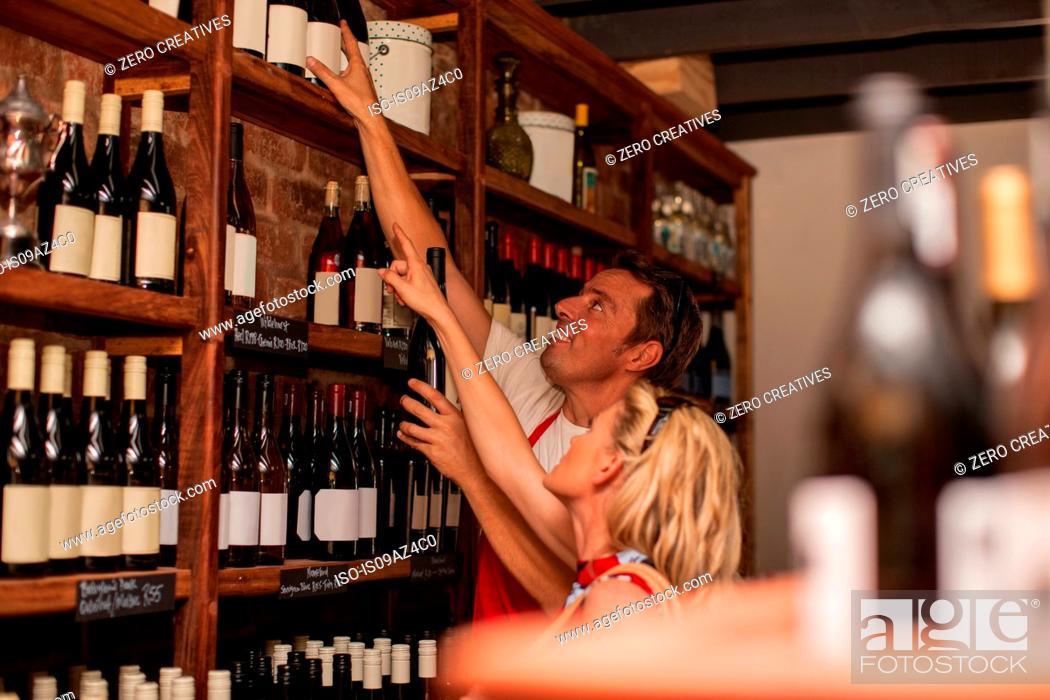 Stock Photo: Man in wine shop helping customer reach wine bottle on top shelf.