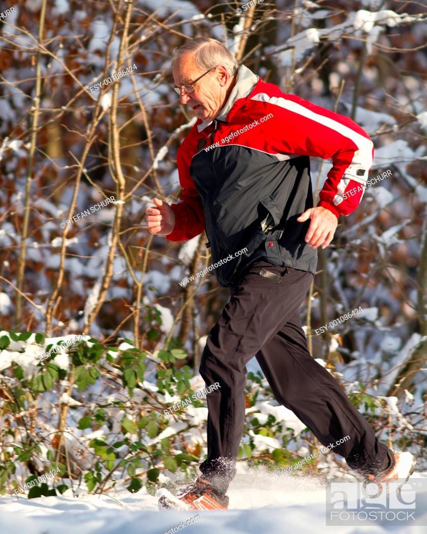 Stock Photo: Senior beim joggen im Schnee.