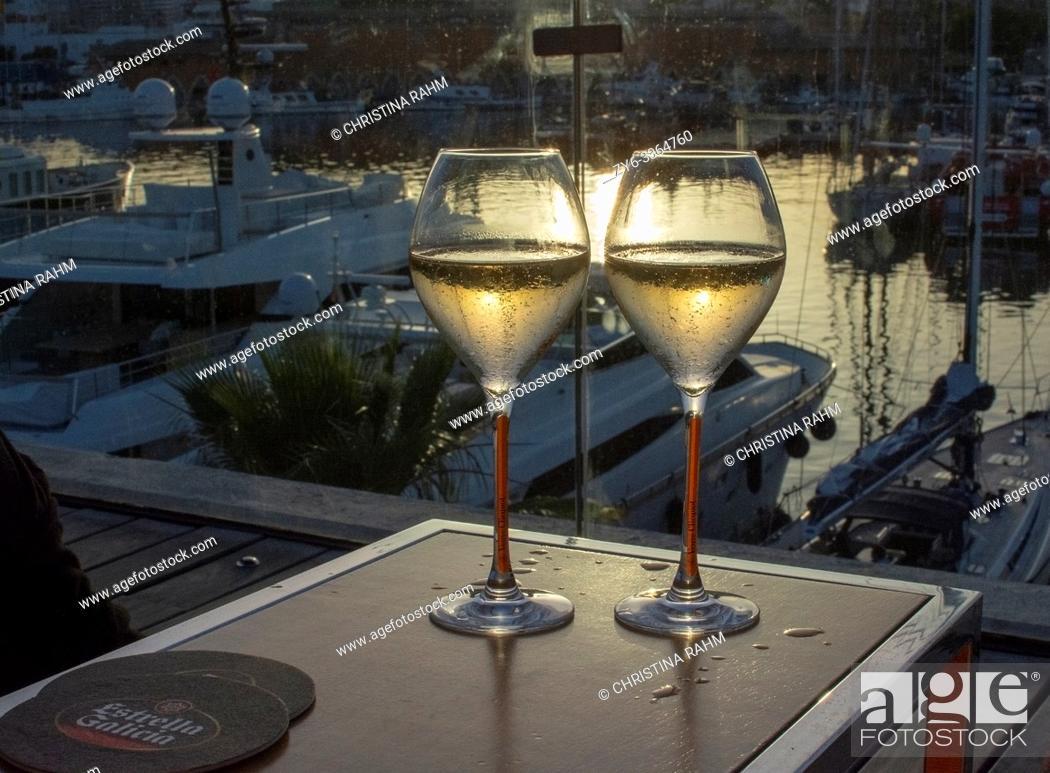 Stock Photo: PALMA DE MALLORCA, SPAIN - JUNE 23, 2019: Two champagne flute glasses Veuve Cliquot at sunset by the marina in sunshine romantic on June 23, 2019 in Mallorca.