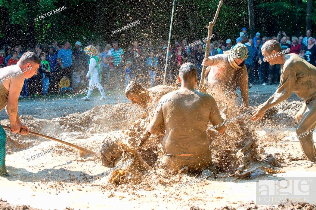 Stock Photo: Participants of the traditional dirty pig festival wallow in a slough near Hergisdorf, Germany, 25 May 2015. With this custom the villagers want to dispel.