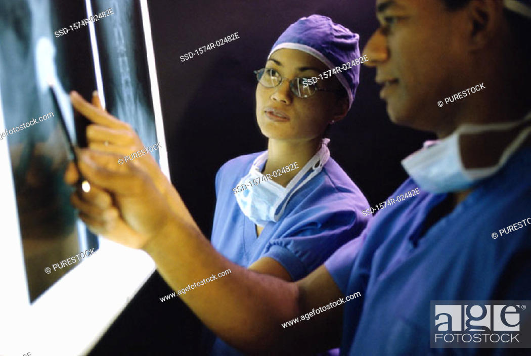 Stock Photo: Male doctor and a female doctor examining an x-ray report.