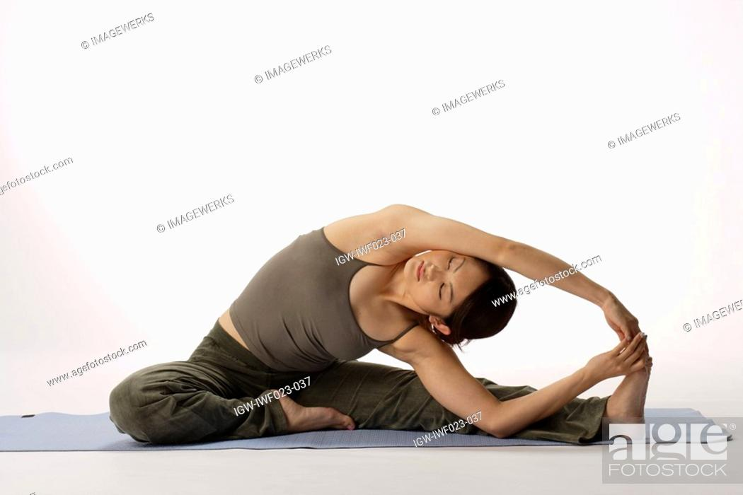 Stock Photo: View of a young woman stretching on a mat.