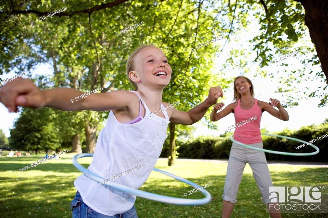 Stock Photo: Mother and daughter with hula-hoop.