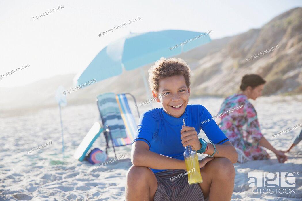 Photo de stock: Portrait smiling, confident boy drinking juice on summer sunny beach.