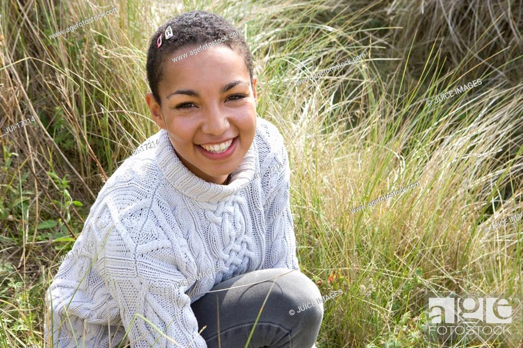 Stock Photo: Portrait of mixed race woman in grass.