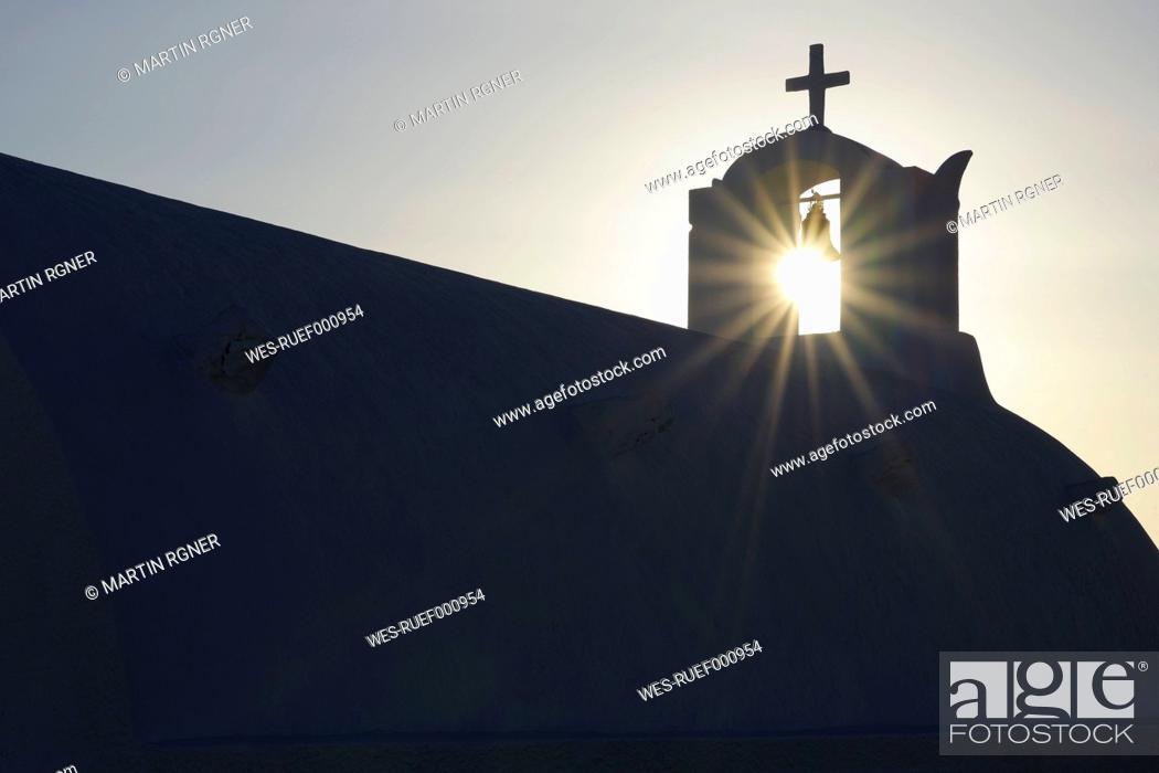 Stock Photo: Greece, Sun shines through belltower in Oia village at Santorini.
