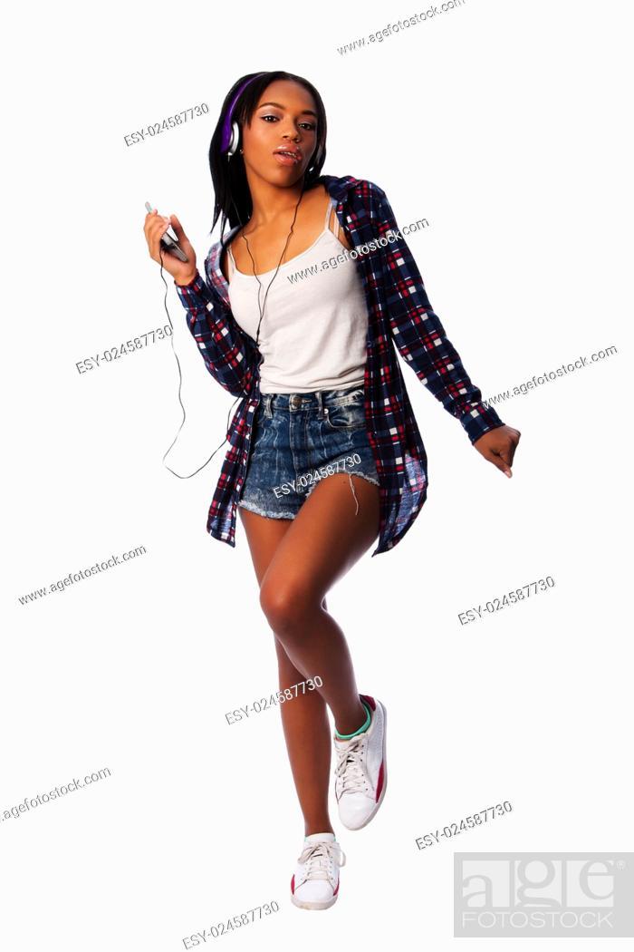 Stock Photo: Beautiful teenager girl listening, dancing and jamming to music on mobile phone wearing purple headphones, on white.