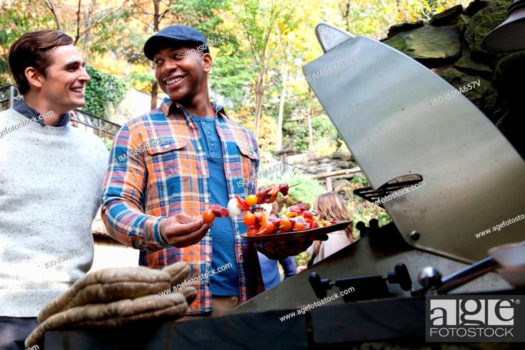 Stock Photo: Men grilling kebabs outdoors.