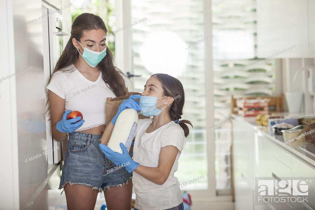 Stock Photo: daughter and mom at home wearing masks and gloves because of the pandemia.