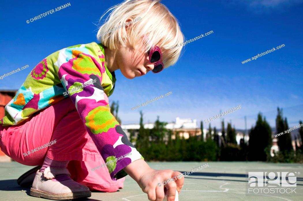 Stock Photo: Girl drawing with sidewalk chalk.