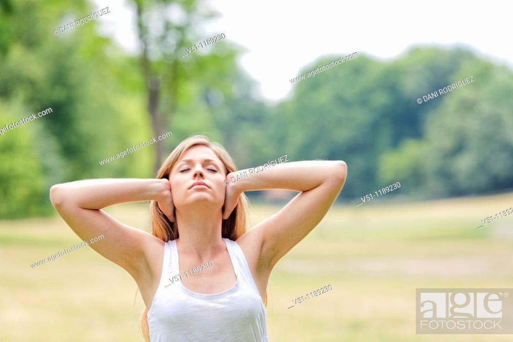 Stock Photo: Portrait of a blonde woman covering her ears in the park.