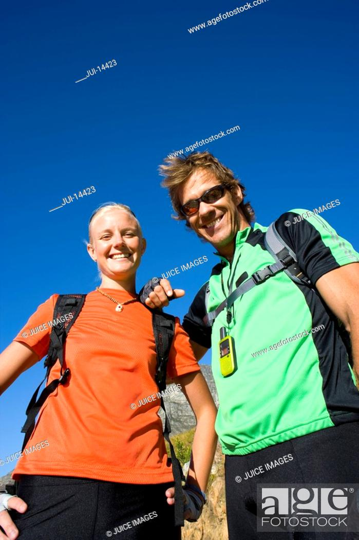 Stock Photo: Young couple hiking, smiling, portrait, low angle view.