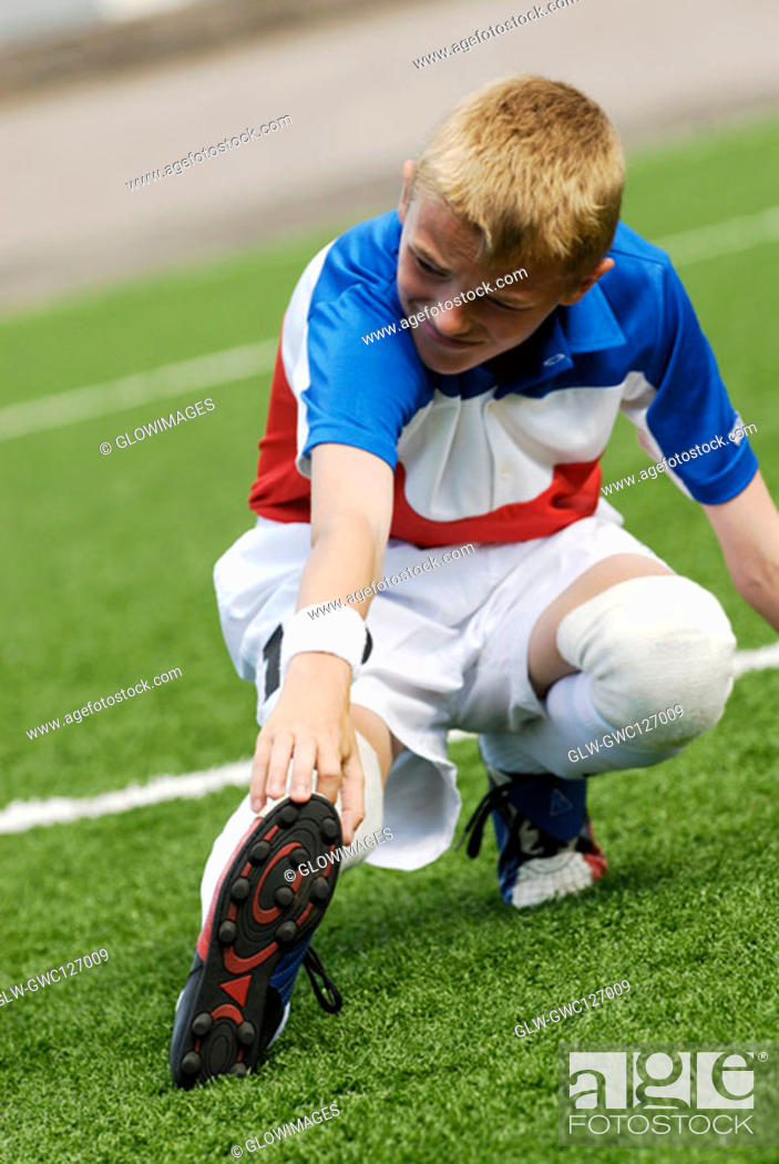 Stock Photo: Close-up of a soccer player touching his toe with his hand.