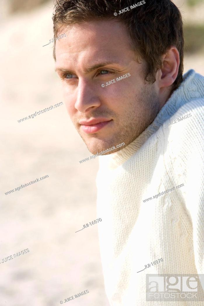 Stock Photo: Young man sitting on beach.